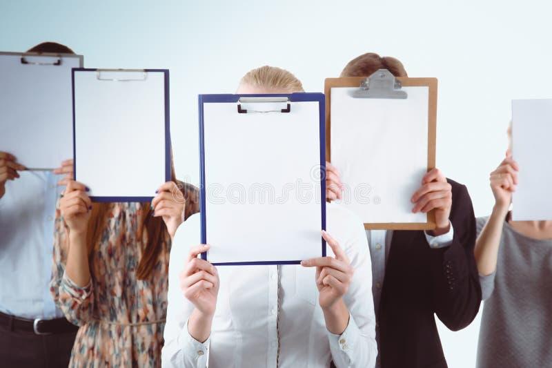 Team die van zakenlui omslagen houden dichtbij gezicht op witte achtergrond businesspeople royalty-vrije stock afbeelding