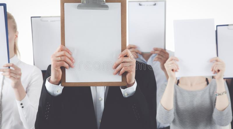 Team die van die zakenlui omslagen houden dichtbij gezicht op witte achtergrond wordt geïsoleerd stock fotografie