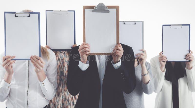 Team die van die zakenlui omslagen houden dichtbij gezicht op witte achtergrond wordt geïsoleerd stock foto's