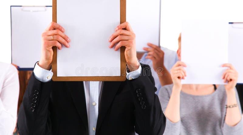 Team die van die zakenlui omslagen houden dichtbij gezicht op witte achtergrond wordt geïsoleerd stock afbeelding