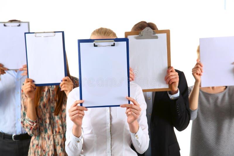 Team die van die zakenlui omslagen houden dichtbij gezicht op witte achtergrond wordt geïsoleerd royalty-vrije stock afbeelding