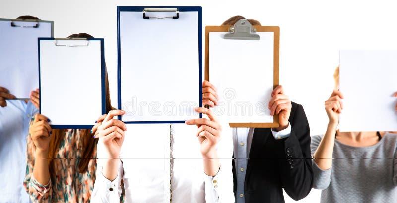 Team die van die zakenlui omslagen houden dichtbij gezicht op witte achtergrond wordt geïsoleerd stock foto