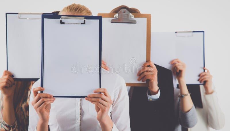 Team die van die zakenlui omslagen houden dichtbij gezicht op witte achtergrond wordt geïsoleerd stock afbeeldingen
