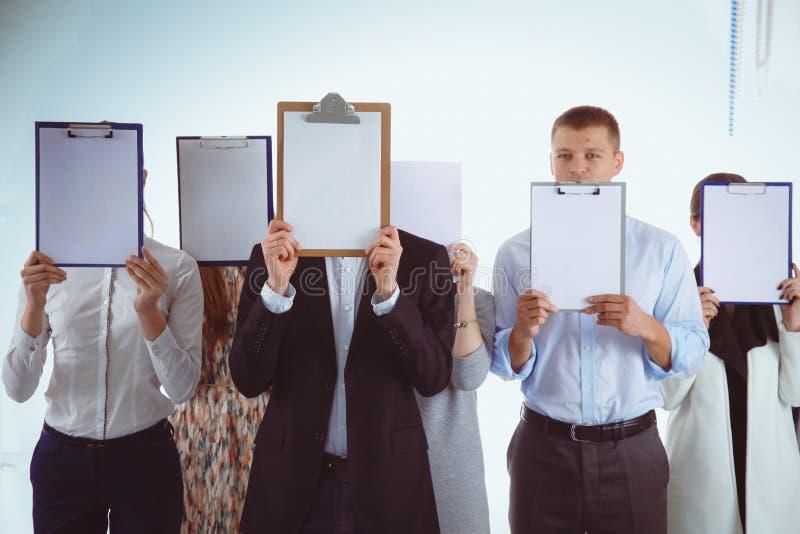 Team die van die zakenlui omslagen houden dichtbij gezicht op witte achtergrond wordt geïsoleerd businesspeople royalty-vrije stock foto