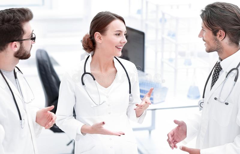 Team of different doctors having conversation. Team of doctors working together on patients file at hospital stock images