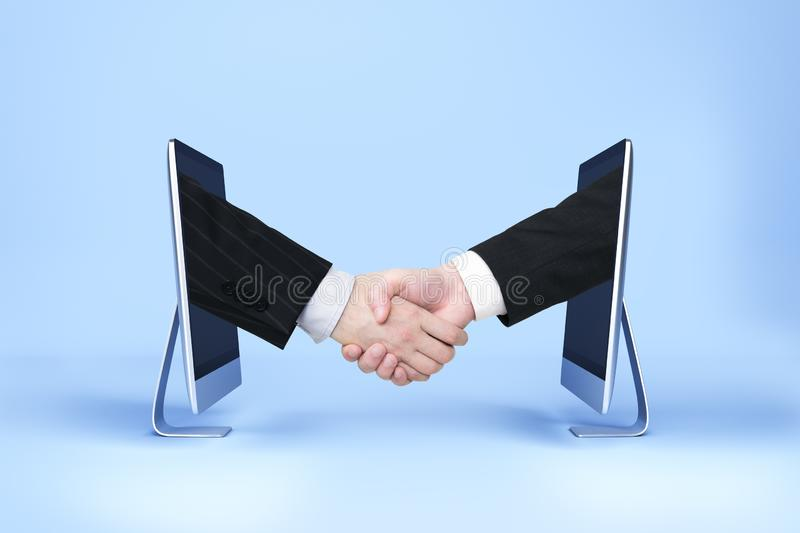 Team and digital business concept. Businessmen shaking hands through computer screens on blue background with shadow. Team and digital business concept stock photography
