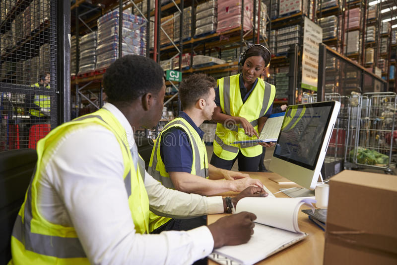 Team discussing warehouse logistics in an on-site office stock images