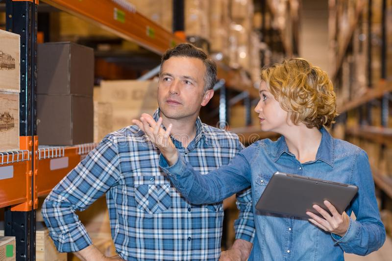 Team discussing while working in warehouse royalty free stock images