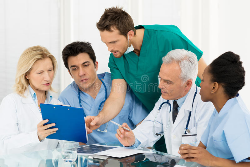 Team Of Doctors Examining Reports stock images
