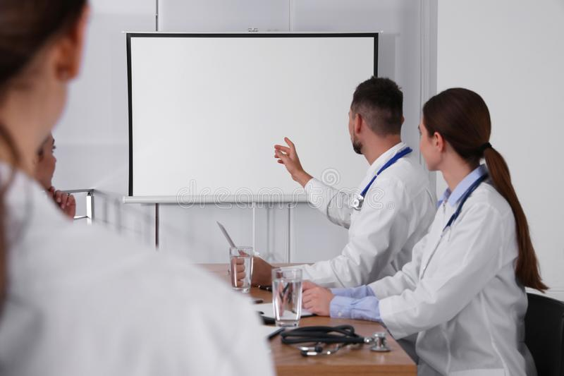 Team of doctors looking at projection screen royalty free stock image
