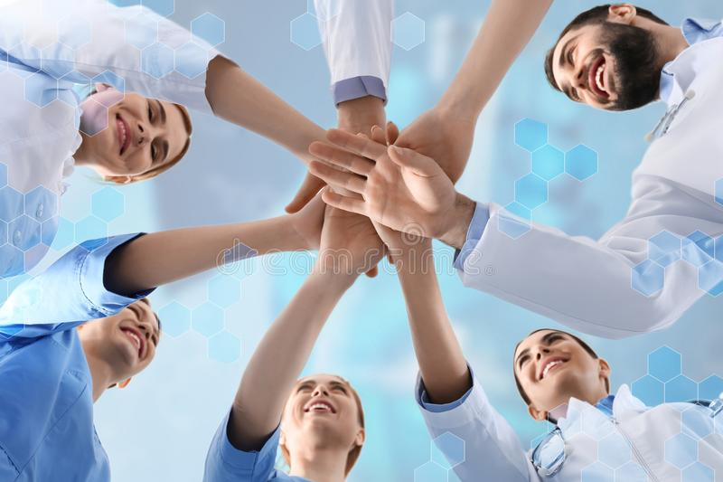 Team of doctors putting hands together, bottom view. Team of doctors putting hands together on color background, bottom view royalty free stock photos