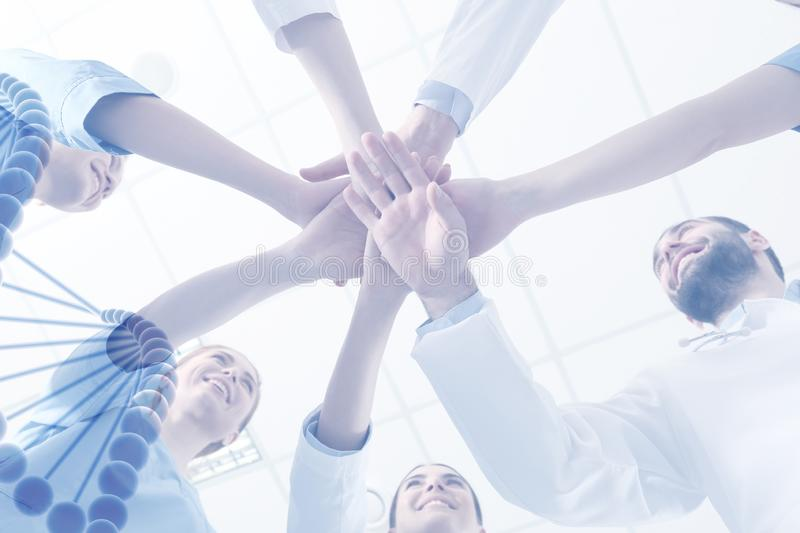 Team of doctors putting hands together on light background. Medical service. Team of doctors putting hands together on light background, bottom view. Medical royalty free stock photos