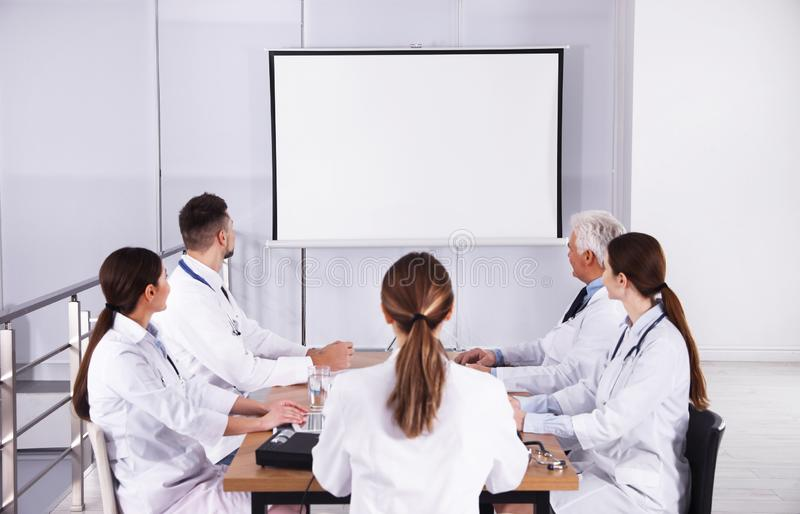 Team of doctors using video projector during conference stock images
