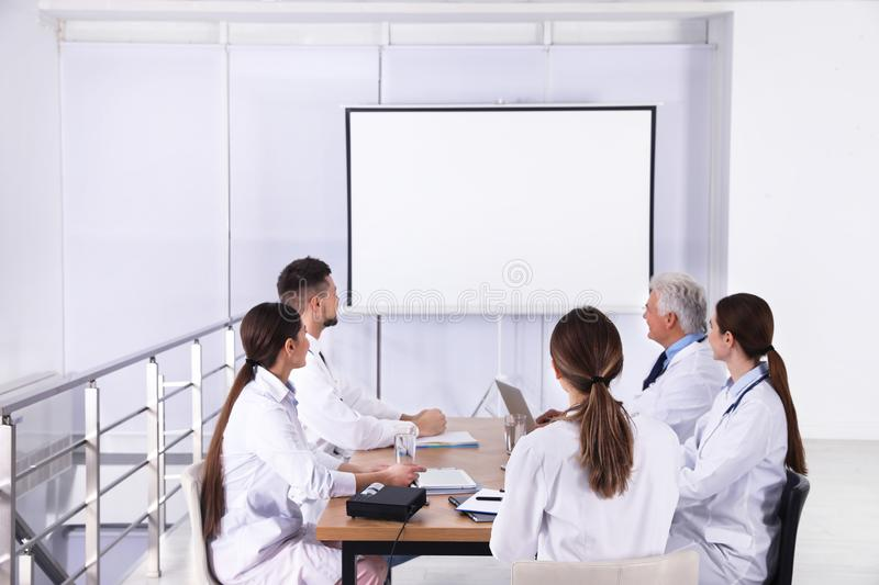 Team of doctors using video projector during conference stock photos