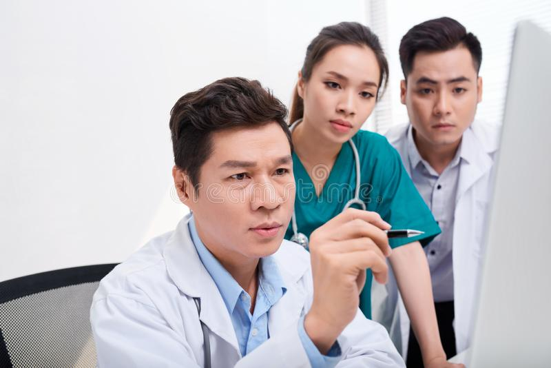 Team of doctors working and having on laptop in medical office royalty free stock image