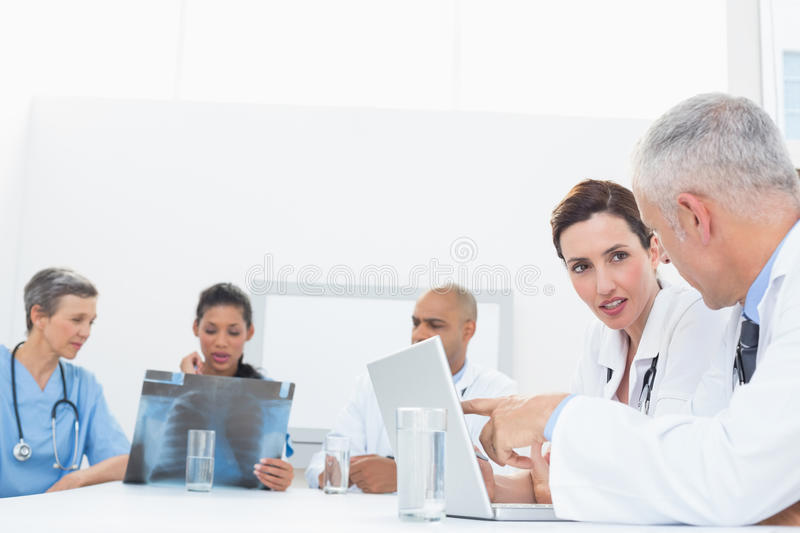 Team of doctors working on laptop and analyzing xray. In medical office royalty free stock photos