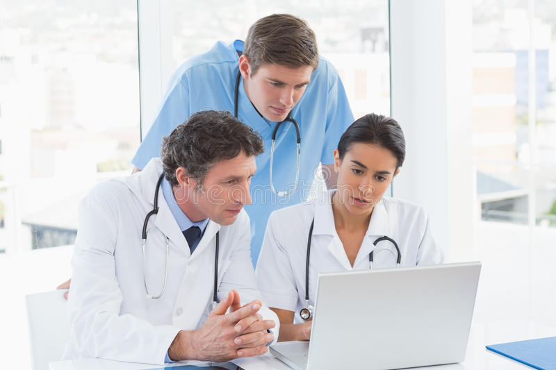 Team Of Doctors Working On Laptop Computer Stock Photo - Image of ...