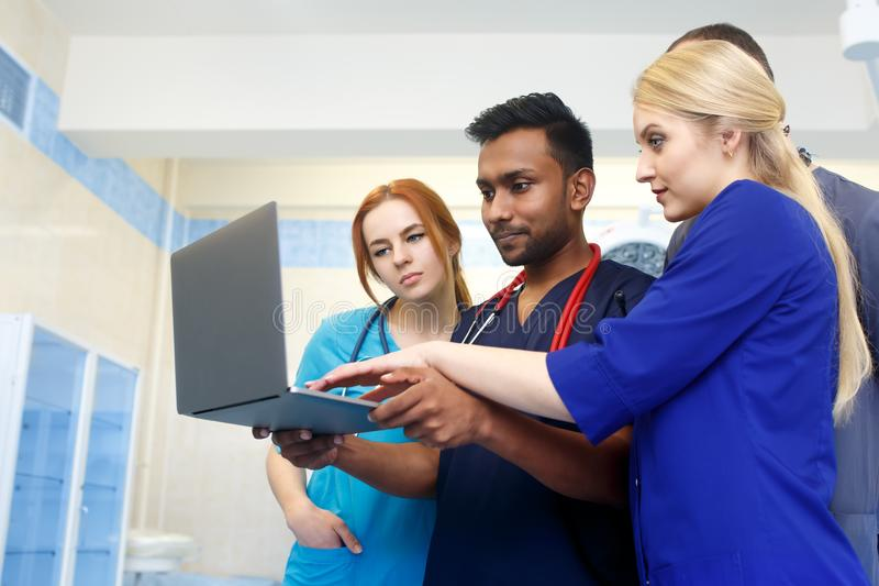 Multiracial team of young doctors working on laptop computer in medical office. royalty free stock photos