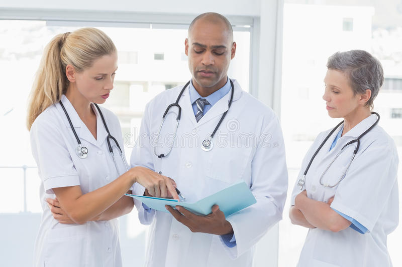 Team Of Doctors Working Together On Patients File Stock Image ...