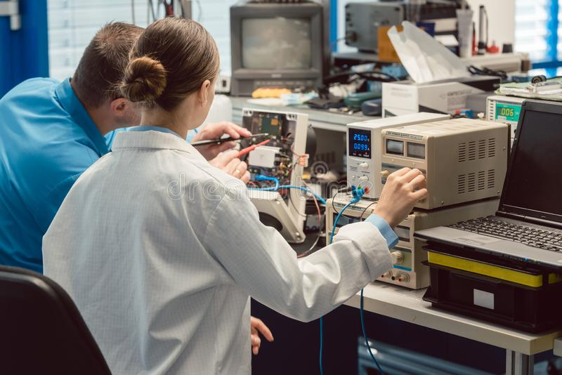 Team of electronic engineers testing a product prototype. On test bench in the lab royalty free stock photography