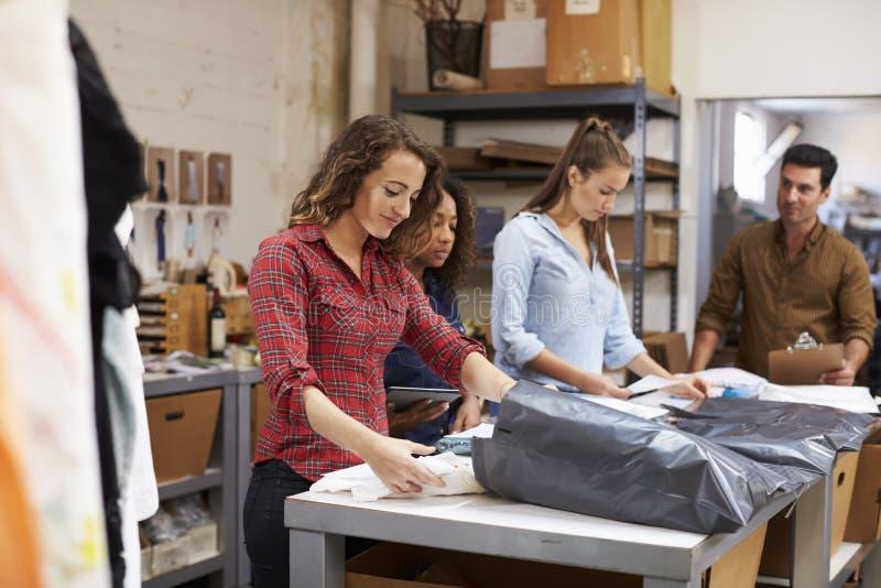 Team em ordens da roupa de uma embalagem da sala do cargo para a distribuição imagens de stock
