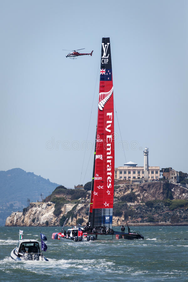 Team Emirates AC 72 Sailboat completes turn as helicopter and race committee boat watch during Louis Vuitton Cup race in San Franc royalty free stock images