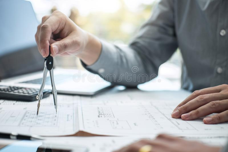 Team of engineering or architect meeting and discussing on blueprint and building model while checking information on sketching. For architectural project stock photography