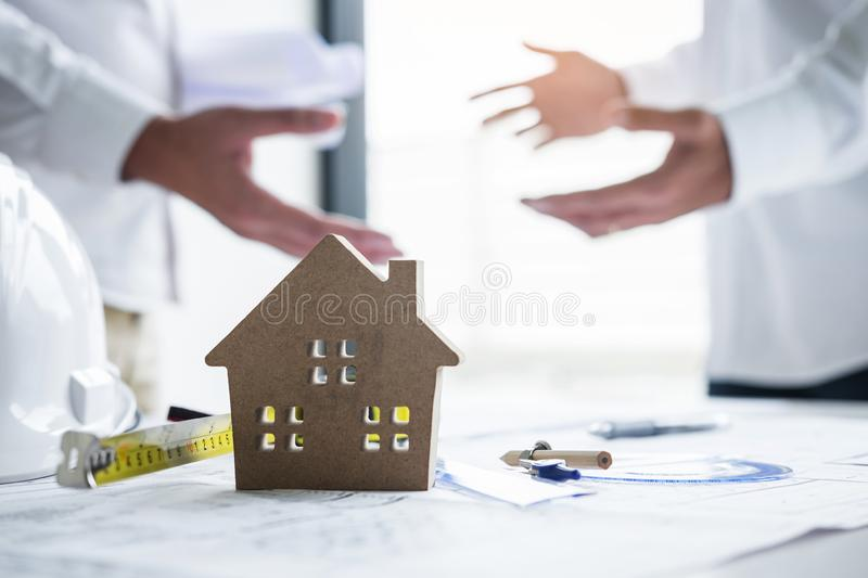 Team of engineering or architect meeting and discussing on blueprint and building model while checking information on sketching. For architectural project stock image