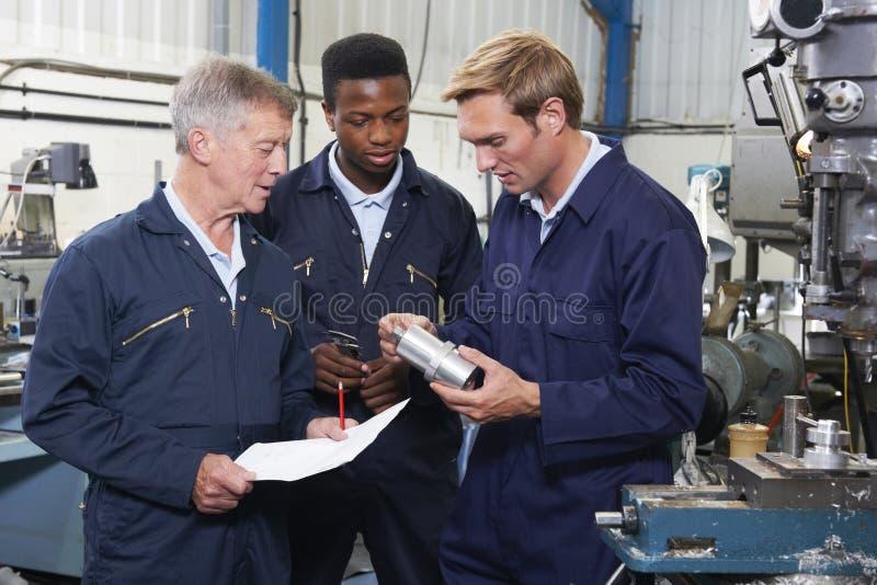 Team Of Engineers Having Discussion na fábrica imagem de stock