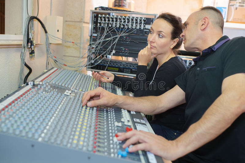 Team engineers working at mixing desk in recording studio stock photography