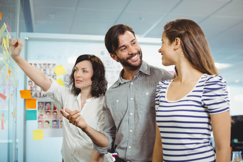 Team of executives discussing over sticky notes. In office stock images
