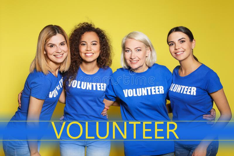 Team of female volunteers in uniform on background royalty free stock photography