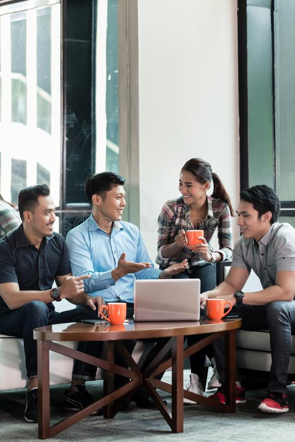 Team of four dedicated employees working together. Team of four dedicated employees sitting in front of a laptop while working together at an innovative business royalty free stock photos