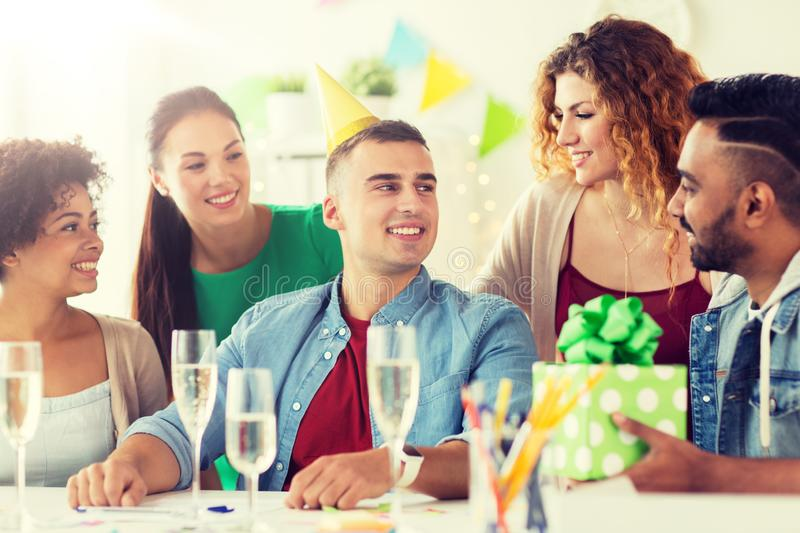 Team greeting colleague at office birthday party stock photo