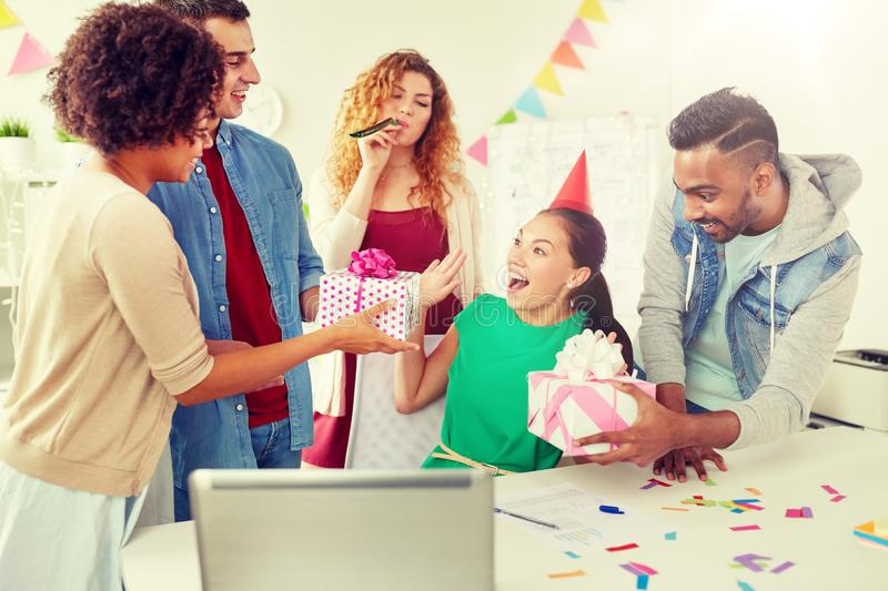 Team greeting colleague at office birthday party royalty free stock photography