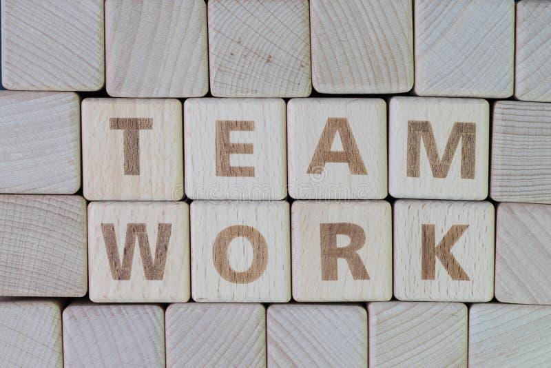 Team, groepswerk de inspanning werken togetther om het doelstellingen concept door kubus houten blok met alfabet te voltooien die stock afbeeldingen