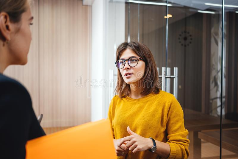 Two positive female employees standing at open space and discuss working moment. Team of handsome business women have meeting at modern office. Two positive stock image