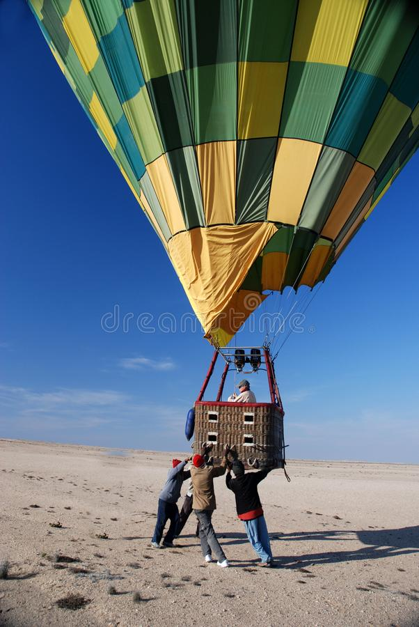Team of helpers ensures a safe landing of a hot air balloon. Hot air balloon is landing in the desert. A team of workers helps for a safe landing