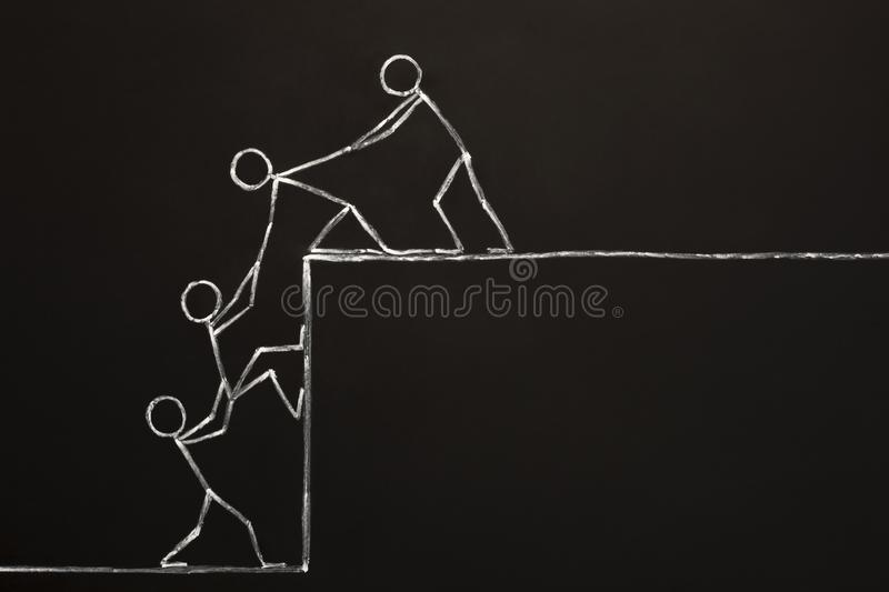Team Helping Each Other To Achieve Success Together. Concept of a business team helping each other to achieve success together drawn with chalk on blackboard stock image