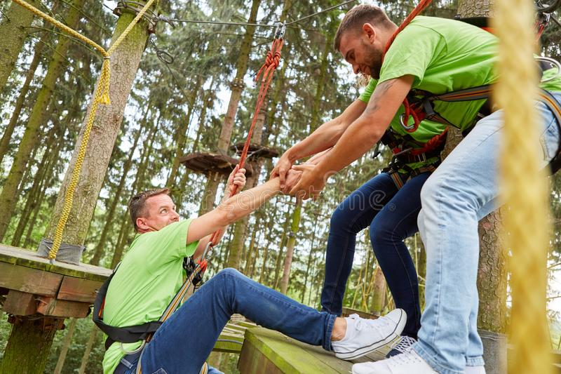 Team helps man to climb the high ropes course royalty free stock photos