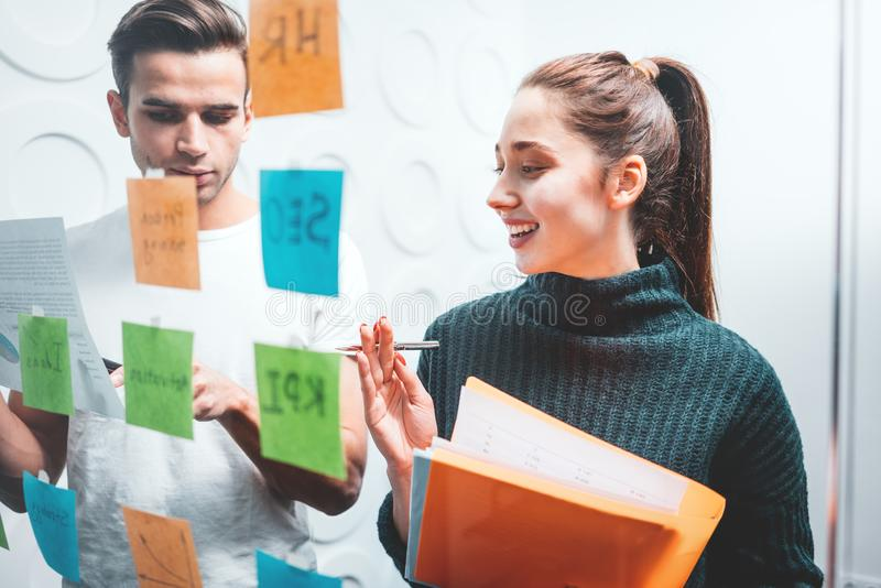 Team of HR manager having meeting standing behind sticky glass wall. Smiling coworkers people brainstorming new business plan posted on a sticky glass note wall stock image
