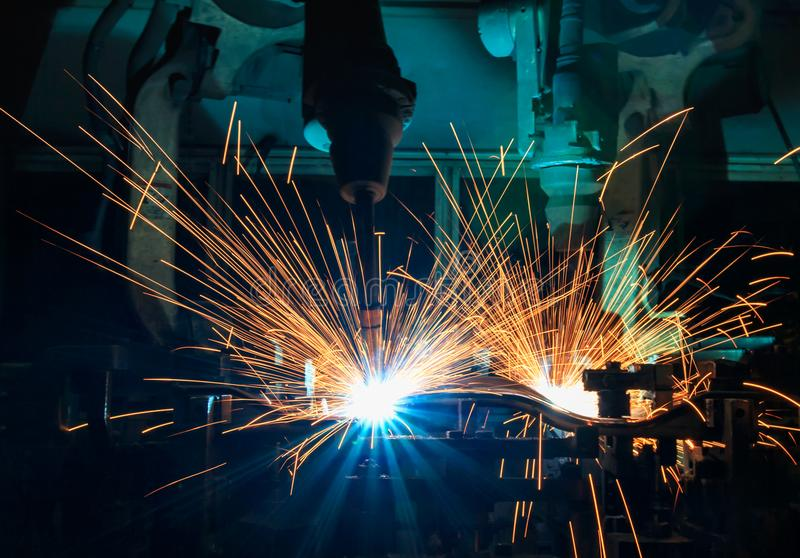 Industrial robot welding are movement welding car part in automotive industrial factory. Team industrial robot welding are movement welding car part in stock photo