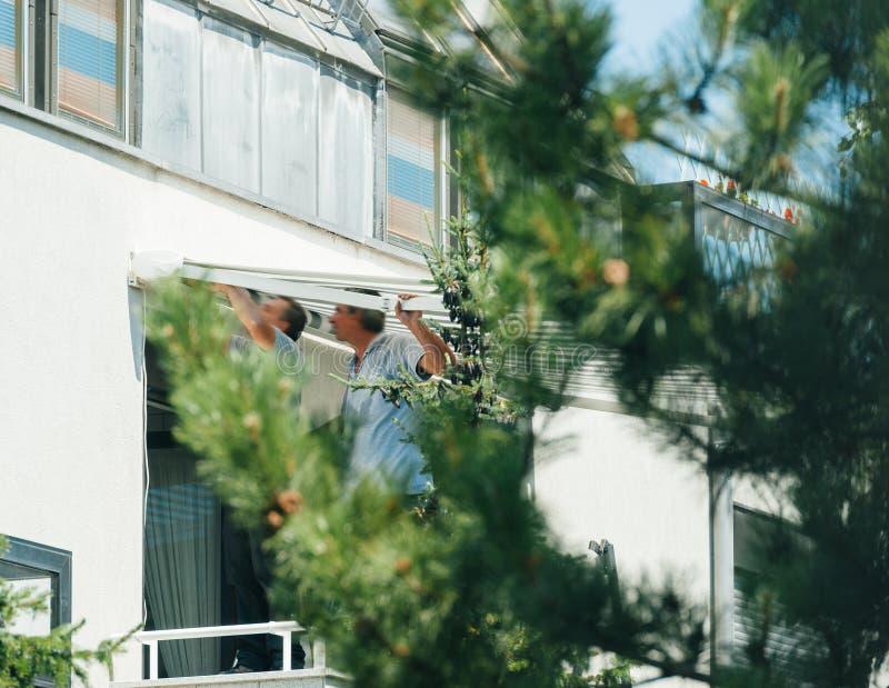 Team instalando o toldo da proteção do sol na janela balckony imagens de stock