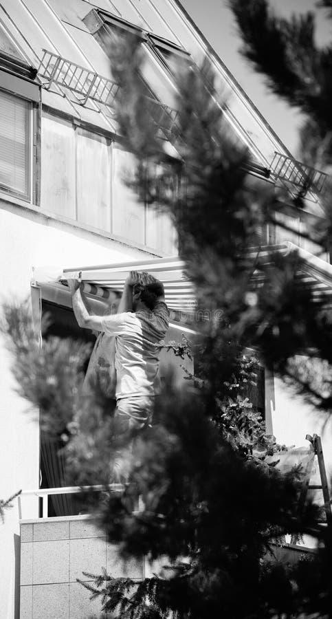 Team instalando o toldo da proteção do sol na janela balckony imagem de stock royalty free