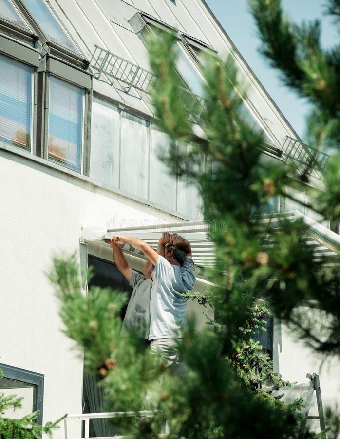 Team instalando o toldo da proteção do sol na janela balckony fotos de stock