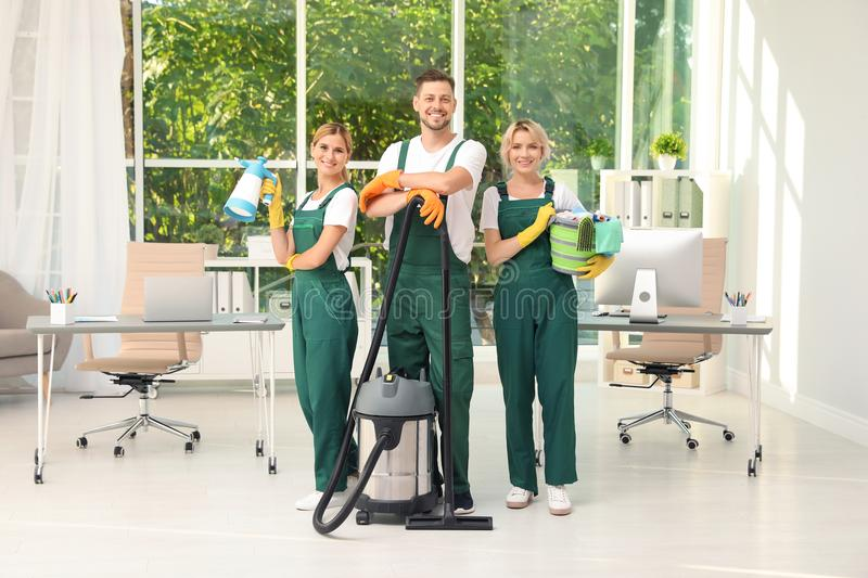 Team of janitors with cleaning supplies. In office stock photo