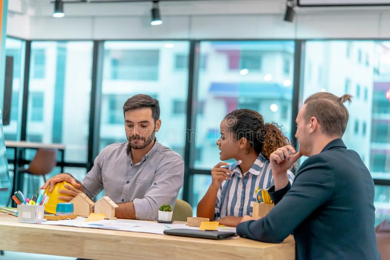 Team jungen Real Estate-Auftragnehmers, der im Büro gedanklich löst lizenzfreies stockfoto