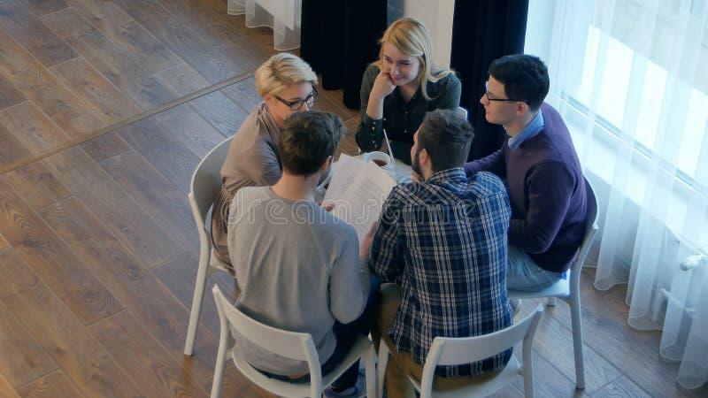 Team Kommunikation, Gruppe von fünf Leuten, die etwas mit Lächeln beim Sitzen am Bürotisch besprechen stockbilder