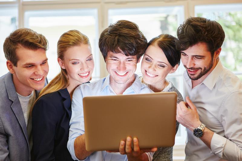 Team with laptop and joy stock image