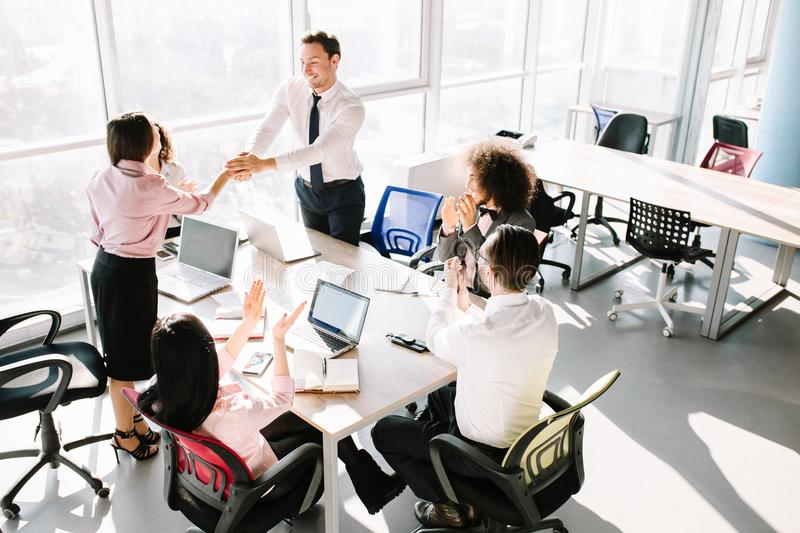 Creating of new important project. Team lead shakes manager hand because of good job. Other managers clapping stock photography